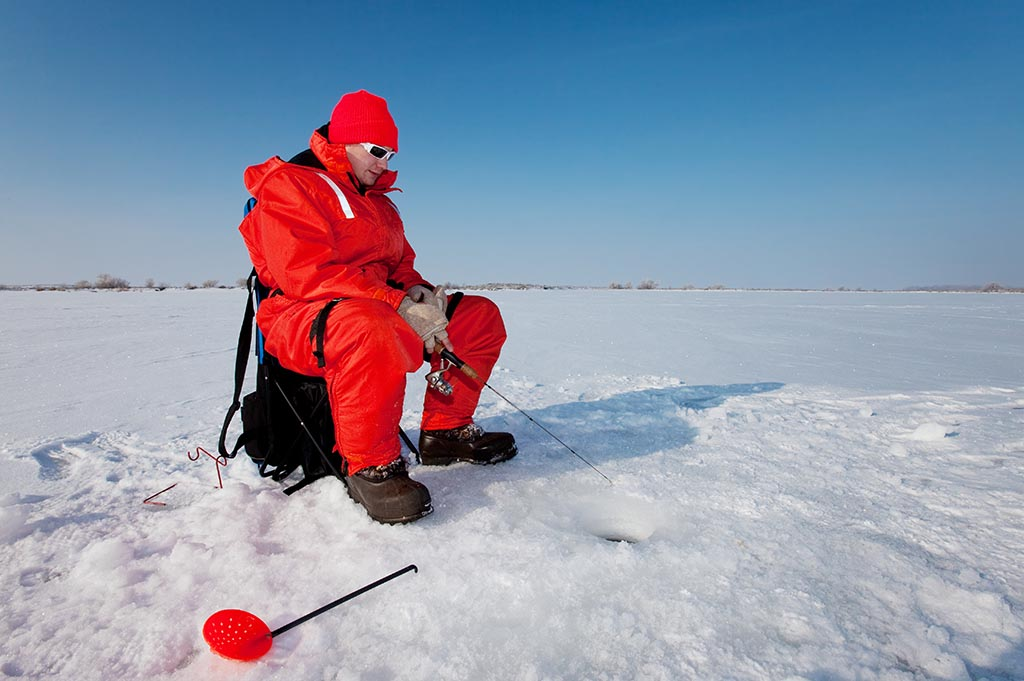 man in red survival suit ice fishing on lake winnipeg