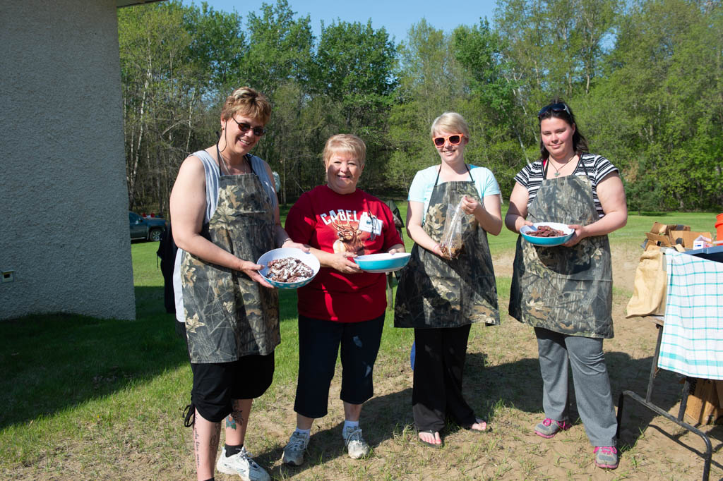 women in camo aprons holding bowls of food