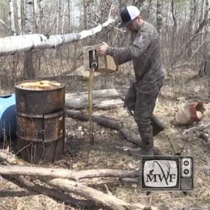 man pouring cooking oil at bear bait station