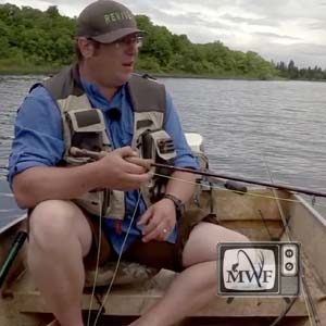 man sitting in boat holding fly rod