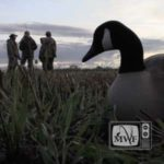 group of people with goose decoy in the foreground