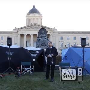 man standing in front of legislative building at lake winnipeg walleye rally