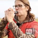 woman blowing into a goose call