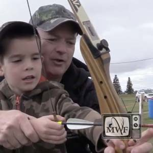 man showing child how to nock an arrow