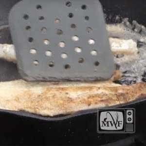 closeup of a spatula flipping a walleye fillet in a cast iron fry pan