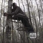 man tying a safety strap onto a tree stand