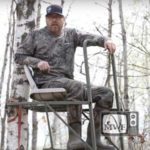 man facing camera sitting in tree stand
