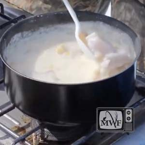 pot of walleye chowder being stirred on a camping stove