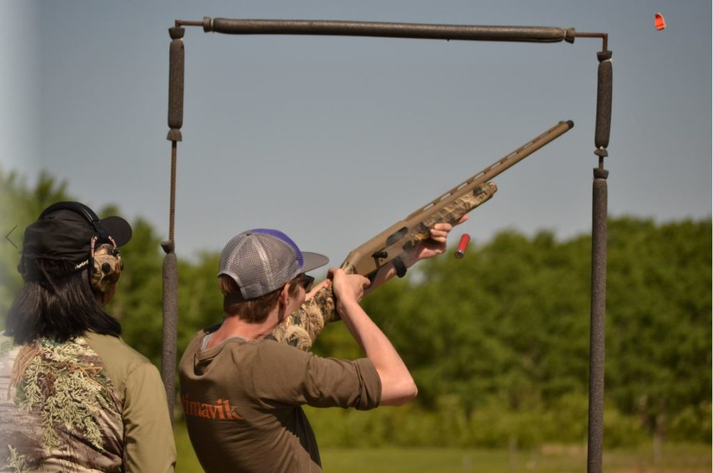 woman shooting a clay while an instructor observes from behind her