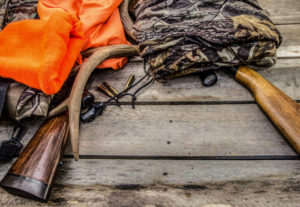 a pile of hunting gear including a rifle, blaze orange, bullets and more lying on a deck