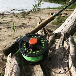 gloomis fly rod and wrx reel lying on driftwood on the bank of the red river