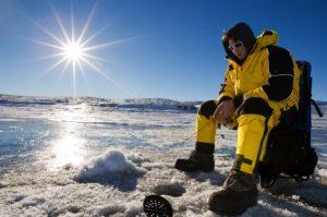 man ice fishing on lake winnipeg