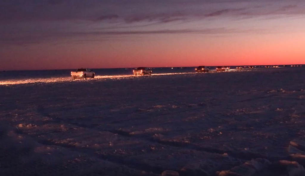 a line of trucks driving onto the ice at the warner road access on lake winnipeg