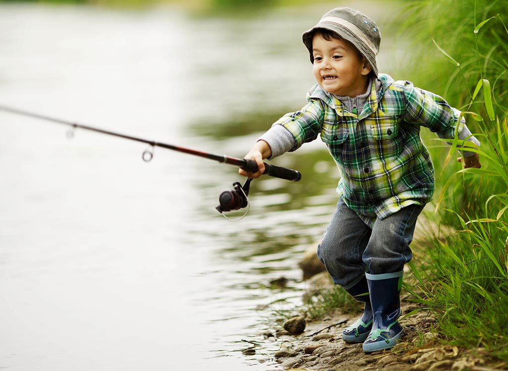 little boy in rubber boots on the bank of a river casting a fishing rod